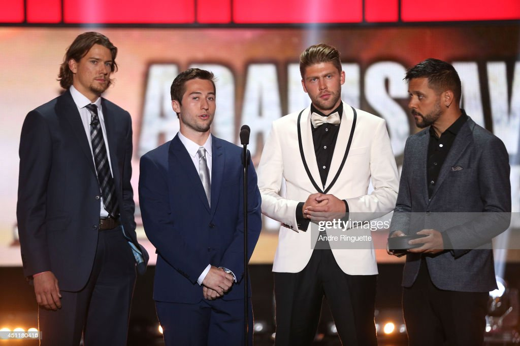 Danny Dekeyser of the Detroit Red Wings, Tyler Johson of the Tampa Bay Lightning, Semyon Varlamov of the Colorado Avalanche and Canadian television and radio personality George Stroumboulopoulos speak onstage to present the Jack Adams Award during the 2014 NHL Awards at the Encore Theater at Wynn Las Vegas on June 24, 2014 in Las Vegas, Nevada.