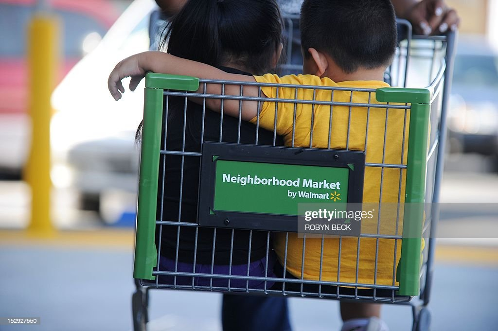 Danny Diaz, 3, (R), rides in a shopping cart with his sister Brianna Diaz, 2 (L), as the arrive with the mother for the Grand Opening of the new Walmart Neighborhood Market in Panorama City, California, a working class area about 13 miles (20km) northwest of Los Angeles, on September 28, 2012. Smaller than Walmart's SuperCenter, the Neighborhood Market resembles a traditional supermarket, selling food, health and beauty products and home cleaning supplies. AFP PHOTO / Robyn Beck