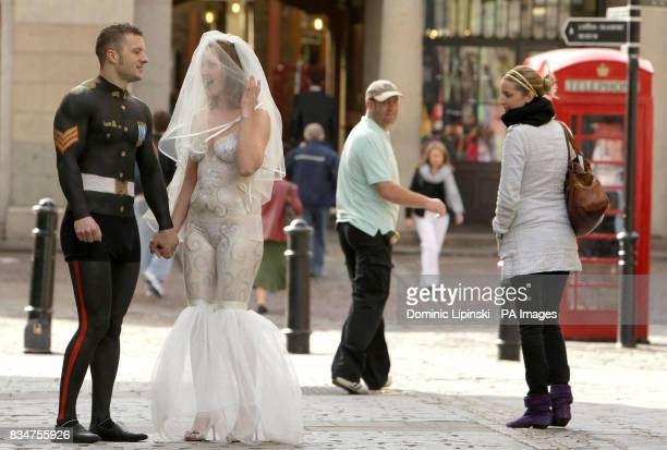 Danny Duggan and Caroline Clark from Sheffield attract attention from members of the public as they walk through Covent Garden London wearing only...