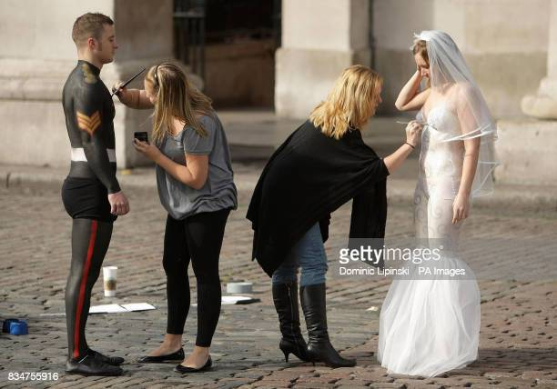 Danny Duggan and Caroline Clark from Sheffield have their bodypaint costumes retouched before walking through Covent Garden London as part of a...