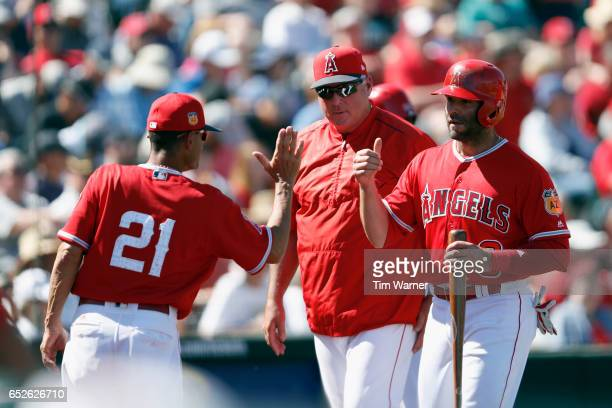 Danny Espinosa of the Los Angeles Angels is greeted by bench coach Dino Ebel and Mike Scioscia after scoring in the second inning against the Seattle...