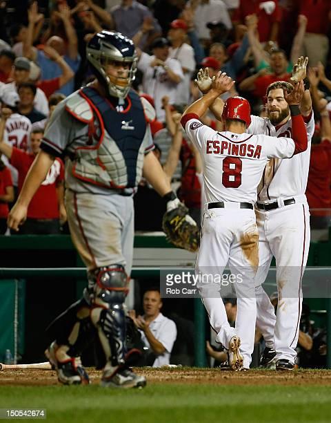 Danny Espinosa of the Washington Nationals celebrates scoring the winning run with teammate Jayson Werth as catcher Brian McCann of the Atlanta...