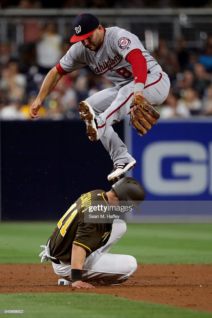 Danny Espinosa #8 of the Washington Nationals leaps over Ryan Schimpf #11 of the San Diego Padres after missing a wide throw during the fifth inning of a baseball game at PETCO Park on June 17, 2016 in San Diego, California.