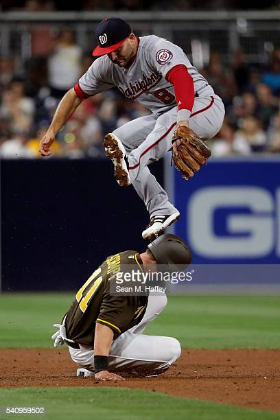 Danny Espinosa of the Washington Nationals leaps over Ryan Schimpf of the San Diego Padres after missing a wide throw during the fifth inning of a...