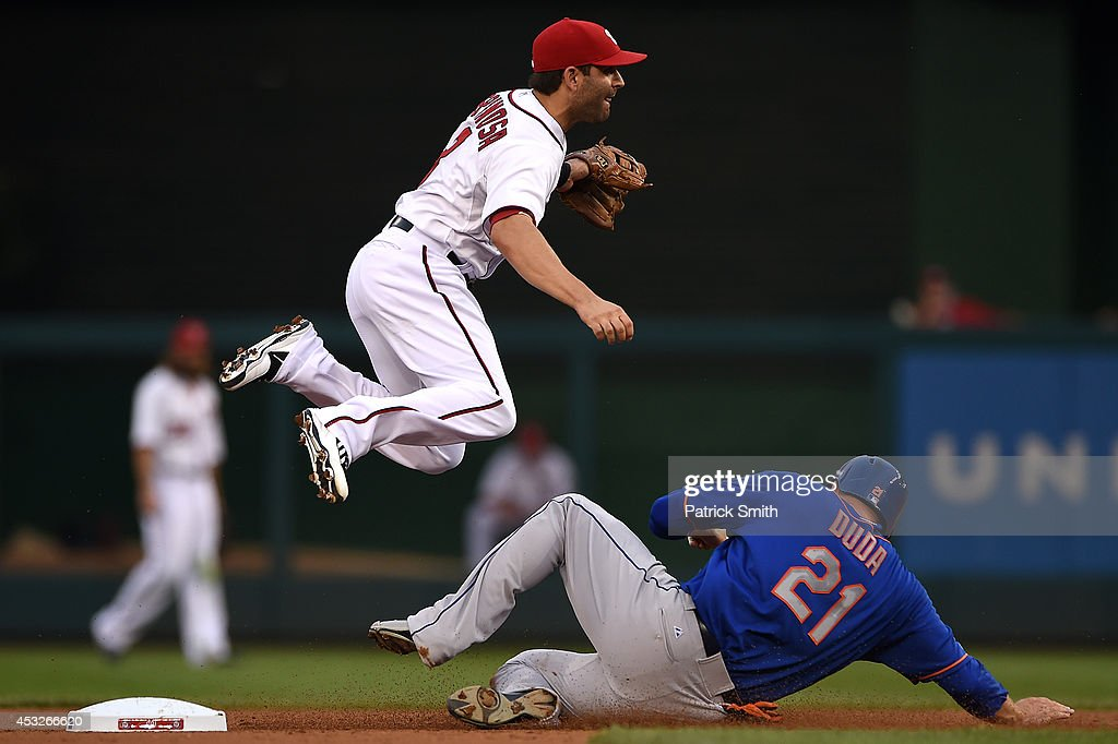 Danny Espinosa of the Washington Nationals turns the double play as Lucas Duda of the New York Mets slides underneath him in the second inning at...