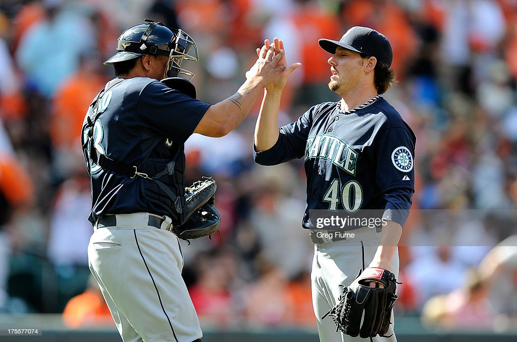 Danny Farquhar #40 of the Seattle Mariners celebrates with <a gi-track='captionPersonalityLinkClicked' href=/galleries/search?phrase=Henry+Blanco&family=editorial&specificpeople=211366 ng-click='$event.stopPropagation()'>Henry Blanco</a> #33 after a 3-2 victory against the Baltimore Orioles at Oriole Park at Camden Yards on August 4, 2013 in Baltimore, Maryland.