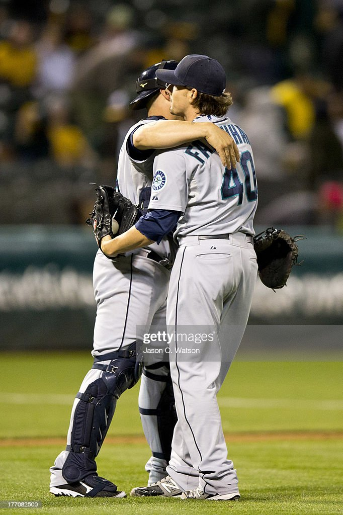 Danny Farquhar #40 of the Seattle Mariners celebrates with <a gi-track='captionPersonalityLinkClicked' href=/galleries/search?phrase=Humberto+Quintero&family=editorial&specificpeople=226980 ng-click='$event.stopPropagation()'>Humberto Quintero</a> #35 after the game against the Oakland Athletics at O.co Coliseum on August 20, 2013 in Oakland, California. The Seattle Mariners defeated the Oakland Athletics 7-4.