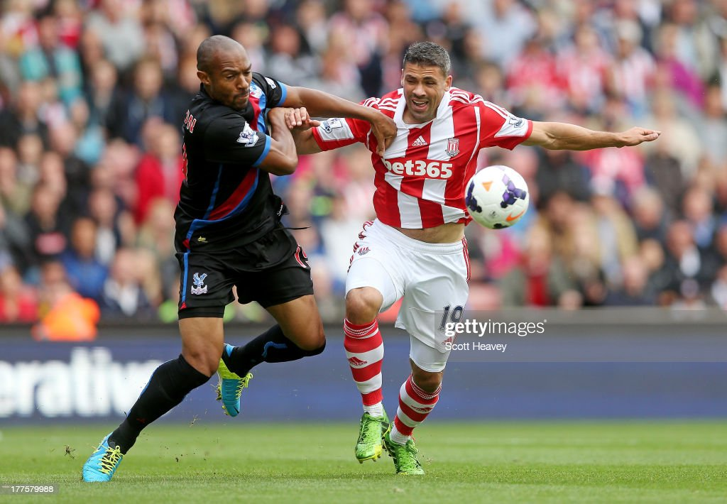 Danny Gabbidon of Crystal Palace (L) holds off Jonathan Walters of Stoke during the Barclays Premier League match between Stoke City and Crystal Palace at Britannia Stadium on August 24, 2013 in Stoke on Trent, England.