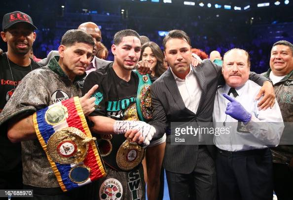 Danny Garcia poses with the referee and promoter Oscar De La Hoya after defeated Zab Judah during the WBA Super and WBC Super Lightweight title fight...