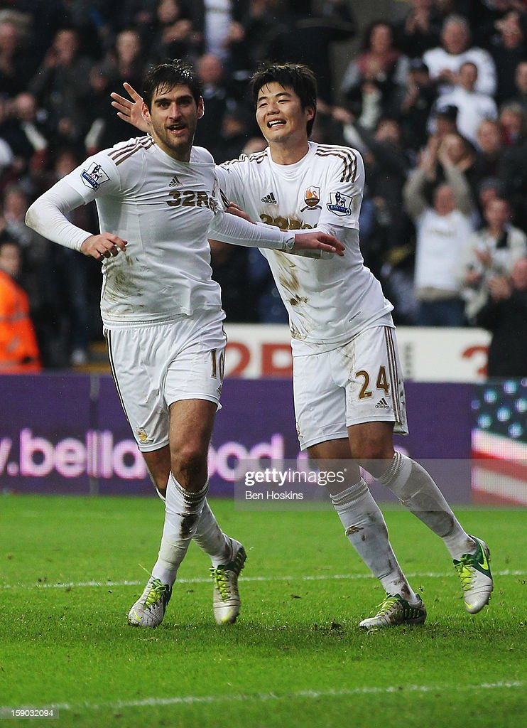 Danny Graham of Swansea City (L) celebrates with <a gi-track='captionPersonalityLinkClicked' href=/galleries/search?phrase=Ki+Sung-Yong&family=editorial&specificpeople=4252298 ng-click='$event.stopPropagation()'>Ki Sung-Yong</a> as he scores their second goal during the FA Cup with Budweiser Third Round match between Swansea City and Arsenal at Liberty Stadium on January 6, 2013 in Swansea, Wales.
