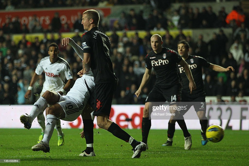 Danny Graham (L) of Swansea City hooks in the second goal as <a gi-track='captionPersonalityLinkClicked' href=/galleries/search?phrase=Brede+Hangeland&family=editorial&specificpeople=618174 ng-click='$event.stopPropagation()'>Brede Hangeland</a> (2L) of Fulham fails to block during the Barclays Premier League match between Swansea City and Fulham at the Liberty Stadium on December 10, 2011 in Swansea, Wales.
