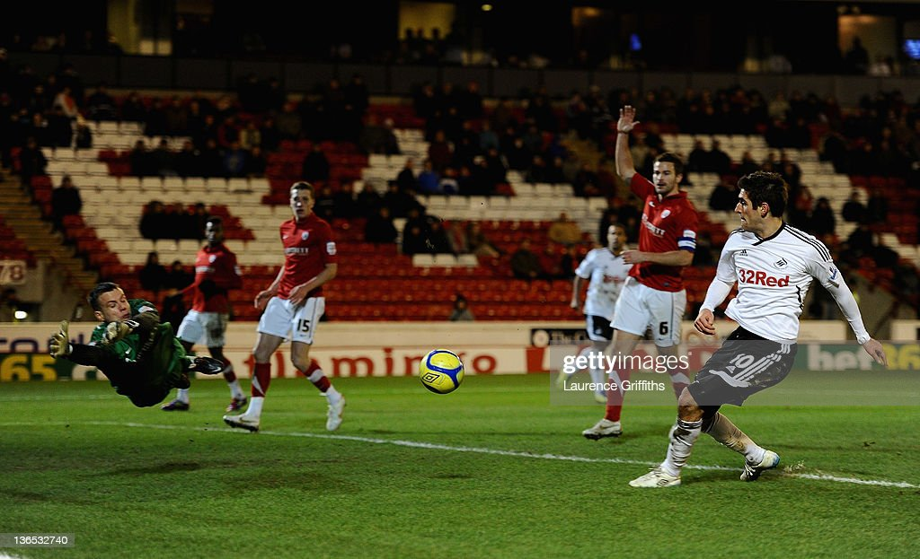Danny Graham of Swansea scores the third past a diving Luke Steele of Barnsley during the FA Cup Third Round match sponsored by Budweiser between...