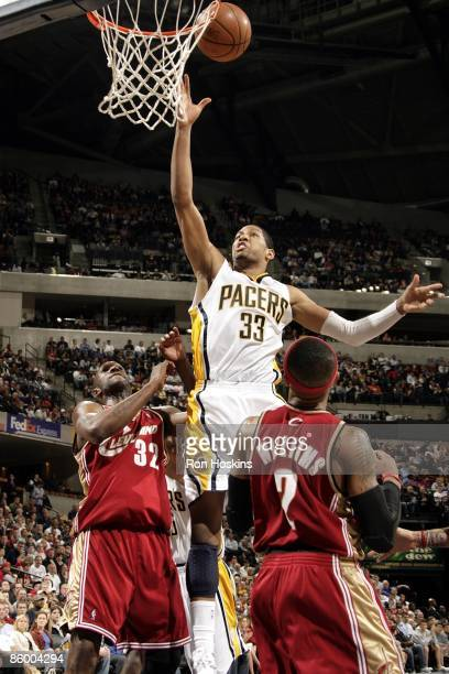 Danny Granger of the Indiana Pacers shoots a layup over Joe Smith and Mo Williams of the Cleveland Cavaliers during the game at Conseco Fieldhouse on...