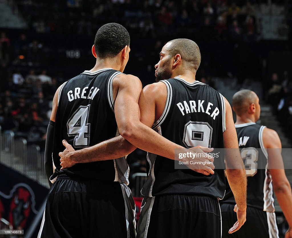 Danny Green #4 and Tony Parker #9 of the San Antonio Spurs stand with each other during the game against the Atlanta Hawks on January 19, 2013 at Philips Arena in Atlanta, Georgia.