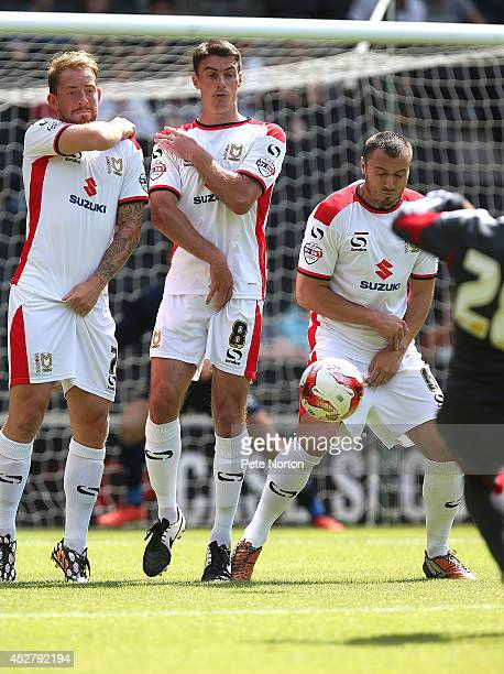 Danny Green Darren Potter and Antony Kay of MK Dons line up to defend a free kick during the PreSeason Friendly match between MK Dons and Nottingham...