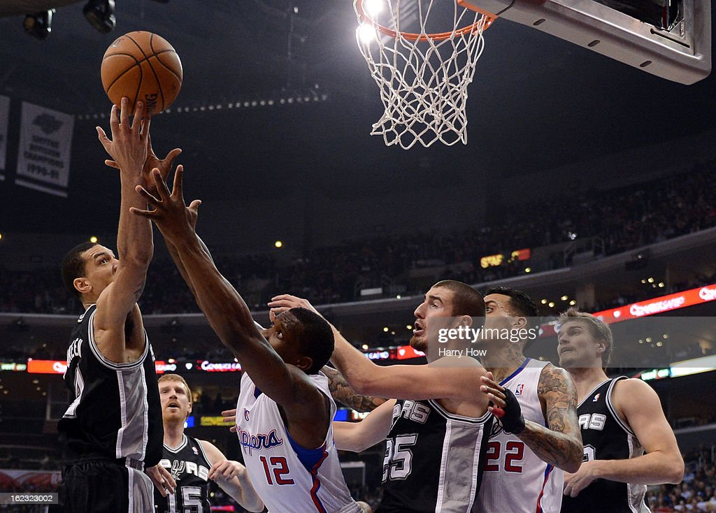 Danny Green #4 of the San Antonio Spurs and Eric Bledsoe #12 of the Los Angeles Clippers reach for a rebound in front of Nando de Colo #25 at Staples Center on February 21, 2013 in Los Angeles, California.