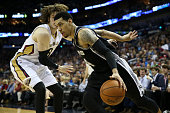 Danny Green of the San Antonio Spurs drives the ball around Luke Babbitt of the New Orleans Pelicans at Smoothie King Center on December 26 2014 in...