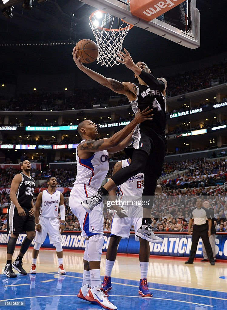 Danny Green #4 of the San Antonio Spurs is fouled as he shoots by Caron Butler #5 of the Los Angeles Clippers at Staples Center on February 21, 2013 in Los Angeles, California.