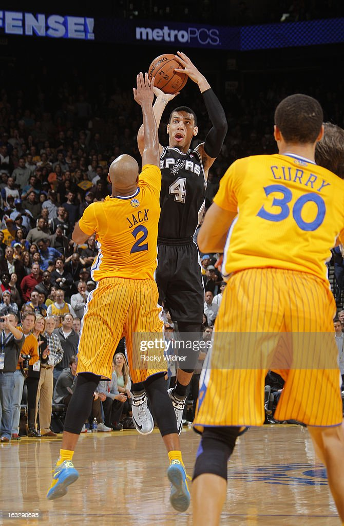 Danny Green #4 of the San Antonio Spurs shoots a three pointer against Jarrett Jack #2 of the Golden State Warriors on February 22, 2013 at Oracle Arena in Oakland, California.