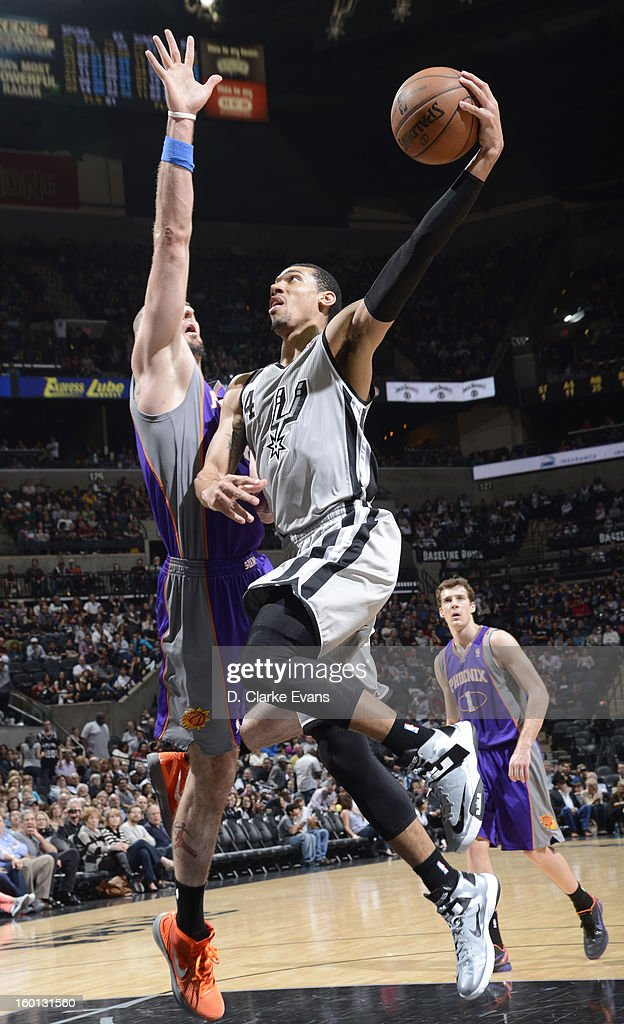 Danny Green #4 of the San Antonio Spurs shoots against Marcin Gortat #4 of the Phoenix Suns on January 26, 2013 at the AT&T Center in San Antonio, Texas.
