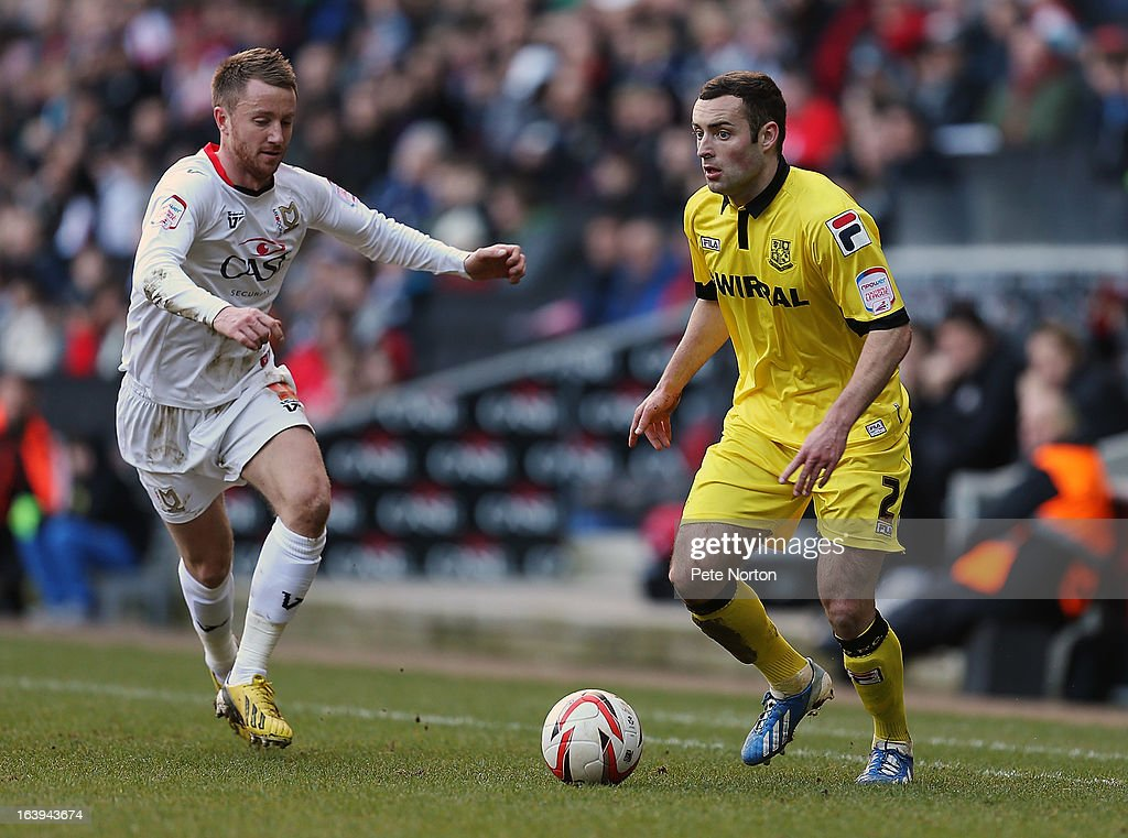 Danny Holmes of Tranmere Rovers looks to play the ball watched by Dean Bowditch of MK Dons during the npower League One match between MK Dons and Tranmere Rovers at Stadium MK on March 16, 2013 in Milton Keynes, England.