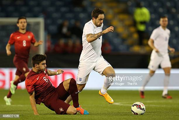 Danny Ings of England leaps over the tackle Ruben Neves of Portugal during the U21 International Friendly match between England and Portugal at Turf...