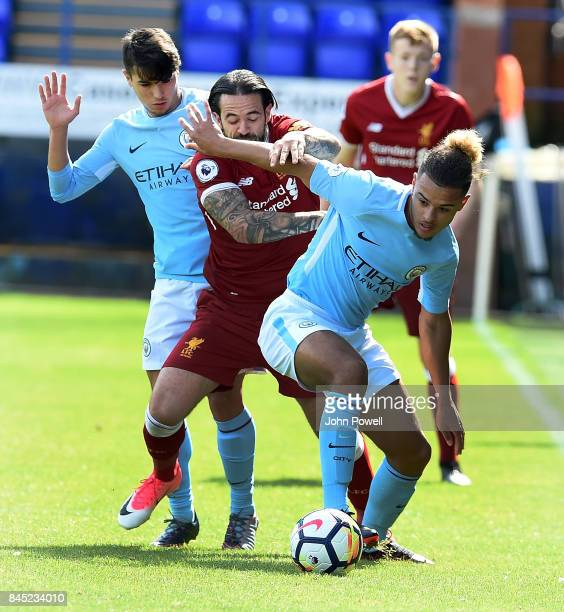 OUT Danny Ings of Liverpool battles with Joel Latibeaudiere of Manchester City during the game at Prenton Park on September 10 2017 in Birkenhead...