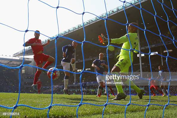 Danny Ings of Liverpool scores Liverpool's first goal past Tim Howard of Everton during the Barclays Premier League match between Everton and...