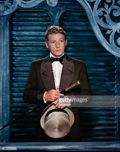 Danny Kaye looking pensive holding hat and cane waist up SEE