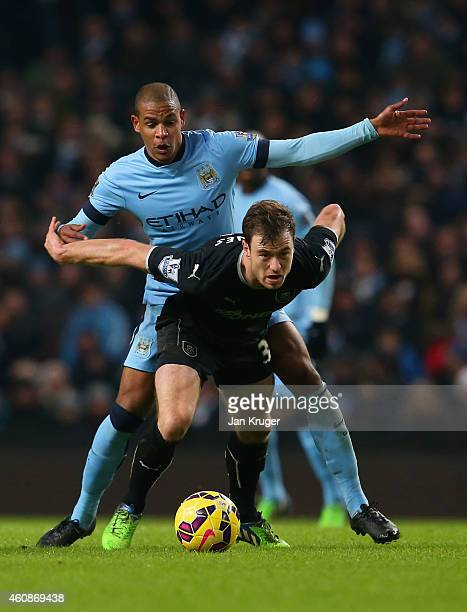 Danny Lafferty of Burnley holds off Fernando of Manchester City during the Barclays Premier League match between Manchester City and Burnley at...
