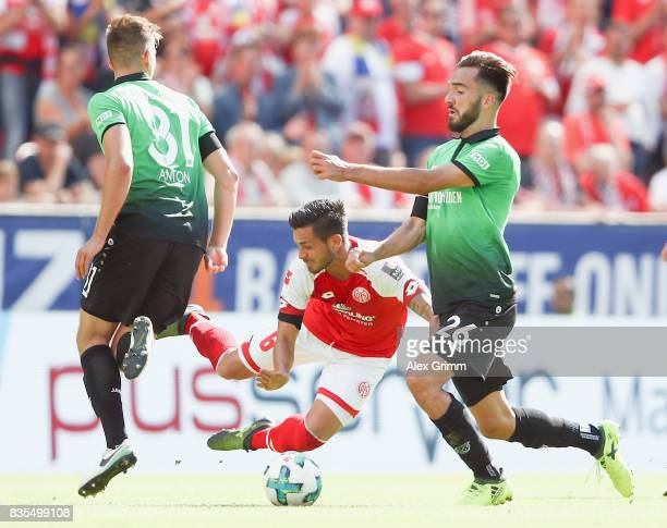 Danny Latza of Mainz is challenged by Waldemar Anton and Kenan Karaman of Hannover during the Bundesliga match between 1 FSV Mainz 05 and Hannover 96...