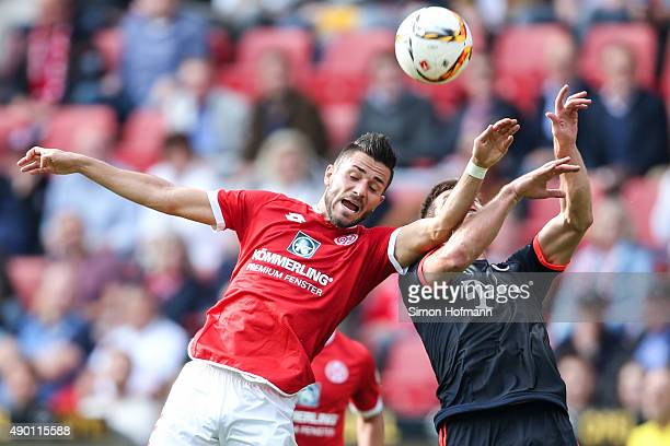 Danny Latza of Mainz jumps for a header with Xabi Alonso of Muenchen during the Bundesliga match between 1 FSV Mainz 05 and FC Bayern Muenchen at...
