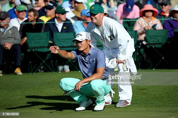 Danny Lee of New Zealand and caddie Mike Hartford line up a putt on the 18th green during the first round of the 2016 Masters Tournament at Augusta...