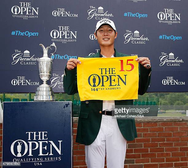 Danny Lee of New Zealand holds a hole flag and stands by the Open Championship Trophy after qualifying for The Open Championship during the final...