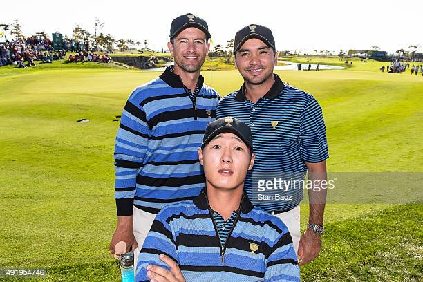 Danny Lee of New Zealand photobombs International Team teammates Jason Day and Adam Scott of Australia following their 1up victory on the 18th hole...