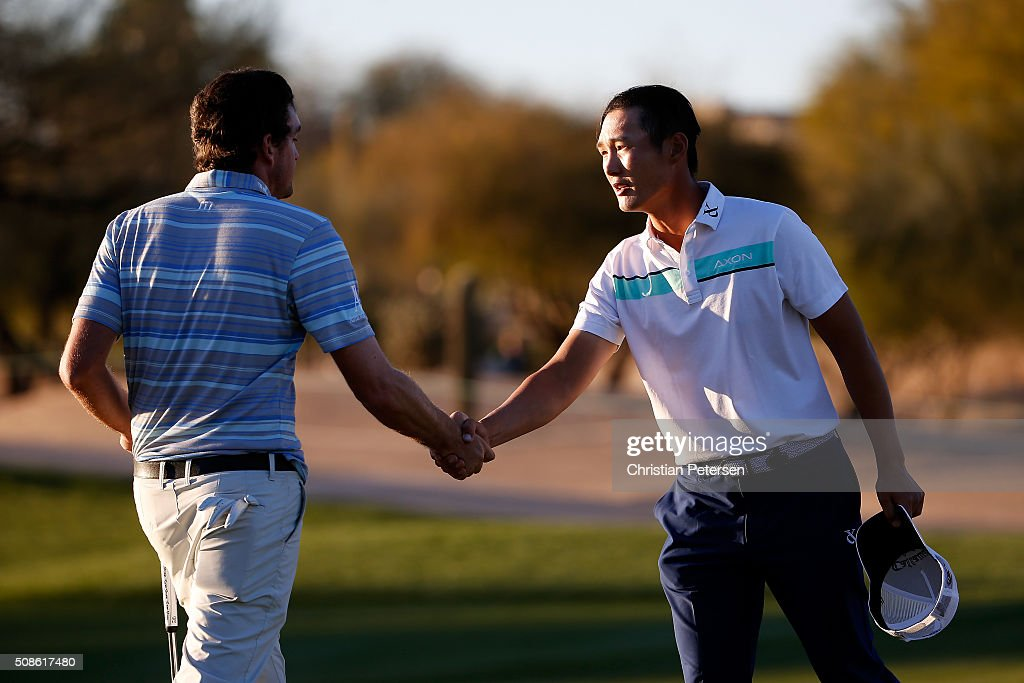 Danny Lee of New Zealand shakes hands with Keegan Bradley after finishing their round on the ninth hole during the second round of the Waste Management Phoenix Open at TPC Scottsdale on February 5, 2016 in Scottsdale, Arizona.
