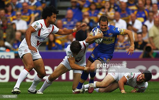 Danny McGuire of Leeds is tackled by Paul Wellens of St Helens during the Carnegie Challenge Cup Semi Final match between Leeds Rhinos and St Helens...
