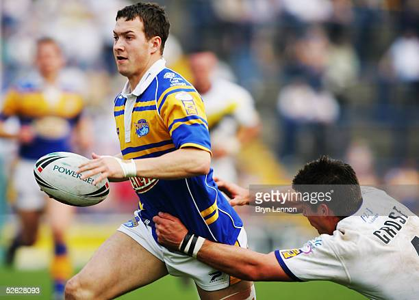Danny McGuire of Leeds is tackled by Warrington's Brent Grose during the Powergen Challenge Cup fourth round match between Leeds Rhinos and...