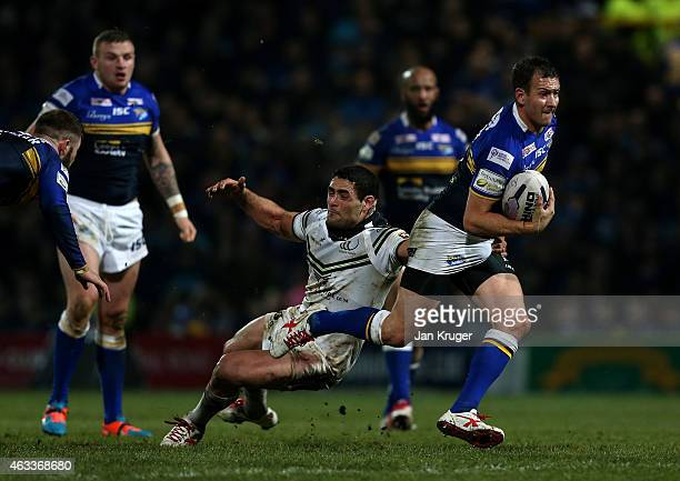 Danny McGuire of Leeds Rhinos beats the tackle of Ben Kavanagh of Widnes Vikings during the First Utility Super League match between Leeds Rhinos and...