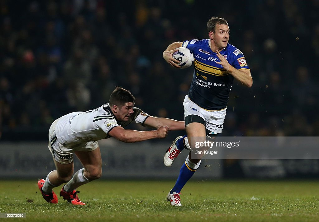 Danny McGuire of Leeds Rhinos breaks through the tackle of Chris Clarkson of Widnes Vikings during the First Utility Super League match between Leeds Rhinos and Widnes Vikings at Headingley Carnegie Stadium on February 13, 2015 in Leeds, England.