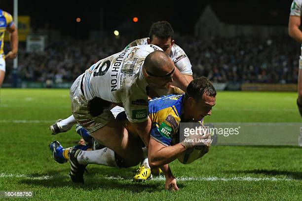 Danny McGuire of Leeds Rhinos dives past a tackle from Danny Houghton and Shannon McDonnell of Hull FC to score his try during the Stobart Super...