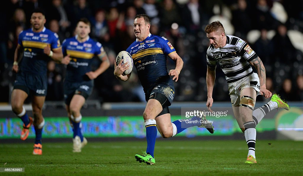 Danny McGuire of Leeds Rhinos gets past Marc Sneyd of Hull FC to score his second try of the match during the First Utility Super League match between Hull FC and Leeds Rhinos at KC Stadium on March 5, 2015 in Hull, England.