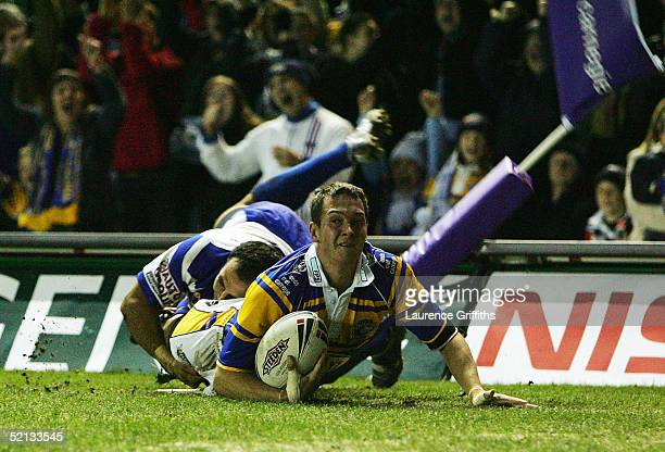 Danny McGuire of Leeds scores under the tackle of Hazem El Masri of Canterbury during the Carnegie World Club Challenge match between Leeds Rhinos...