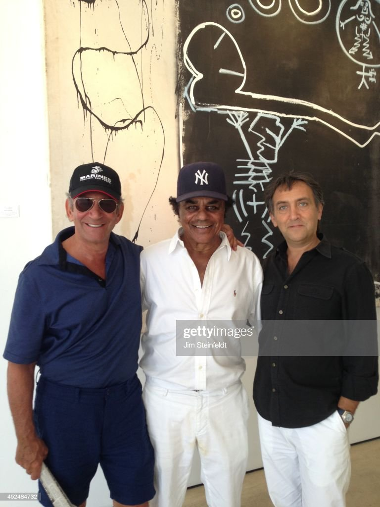 Danny Minnick art exhibit with Marty Berman Johnny Mathis and Gallerie Sparta owner Stephan Sparta in Los Angeles California on July 10 2014