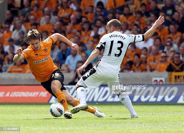 Danny Murphy of Fulham is challenged by Kevin Doyle of Wolves during the Barclays Premier League match between Wolverhampton Wanderers and Fulham at...