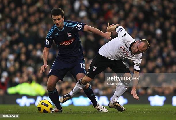 Danny Murphy of Fulham is challenged by Marc Wilson of Stoke City during the Barclays Premier League match between Fulham and Stoke City at Craven...
