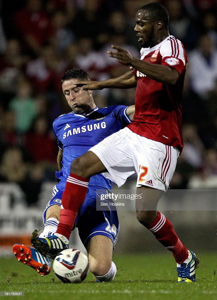Danny N'Guessan of Swindon is tackled by <a gi-track='captionPersonalityLinkClicked' href=/galleries/search?phrase=Gary+Cahill&family=editorial&specificpeople=204341 ng-click='$event.stopPropagation()'>Gary Cahill</a> of Chelsea during the Capital One Cup third round match between Swindon Town and Chelsea at County Ground on September 24, 2013 in Swindon, England.