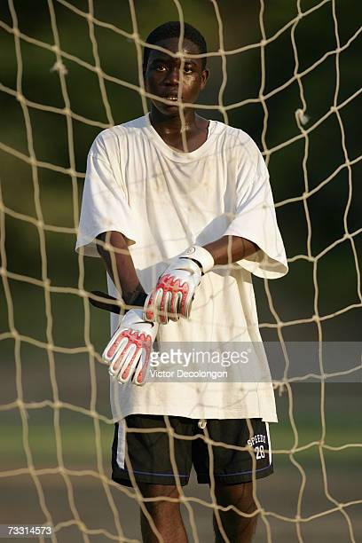 Danny of Ivory Coast aka 'Adu' by his soccer mates puts on his gloves to play goalkeeper for a pickup game on the dirt soccer field at Pan Pacific...