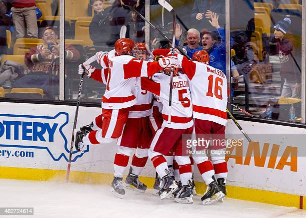 Danny O'Regan of the Boston University Terriers celebrates his double overtime goal with teammates Jack Eichel Evan Rodrigues Matt Grzelcyk and John...