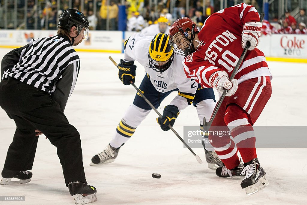 Danny O'Regan #10 of the Boston University Terriers faces off against Alex Guptill #27 of the Michigan Wolverines on October 25, 2013 at Yost Ice Arena in Ann Arbor, Michigan.